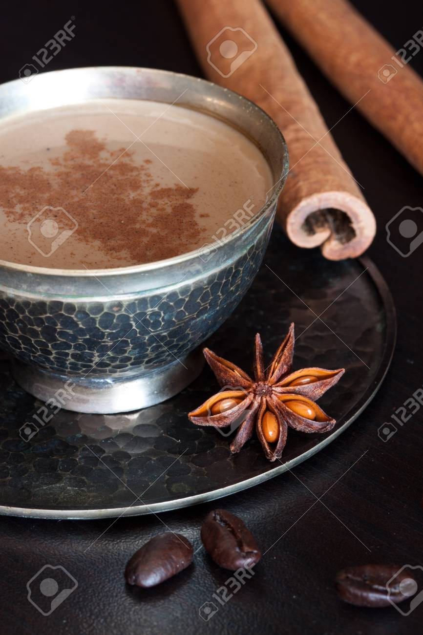 A cup of coffee with  coffe beans and cinnamon stiks Stock Photo - 15544116