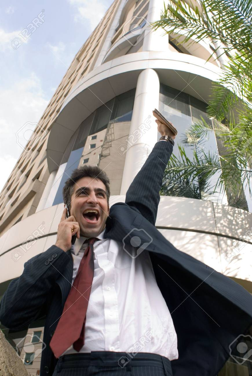 Man in a business suit on the phone pumping his fist in the air Stock Photo - 2687732