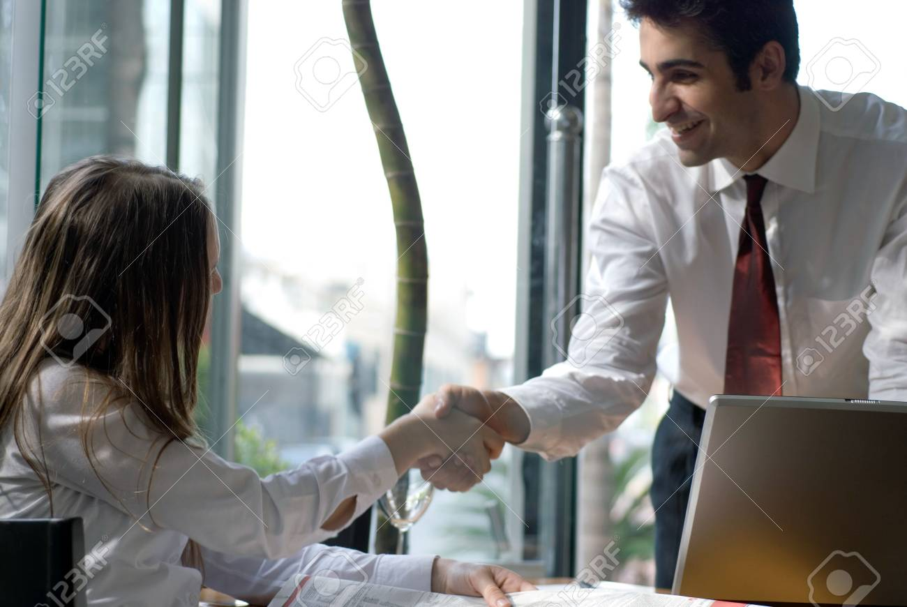 Male and female business people shaking hands over a deal Stock Photo - 2740026