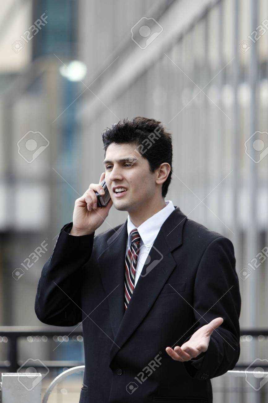 Business man gesturing while talking on his cell phone outdoors Stock Photo - 2789883