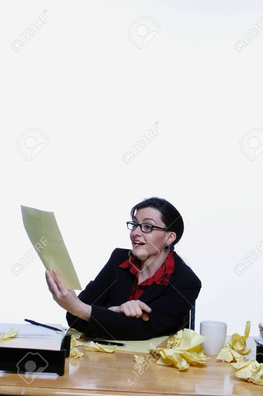 Businesswoman holding up a sheet of yellow legal paper and pointing at it with a smile on her face Stock Photo - 2986770