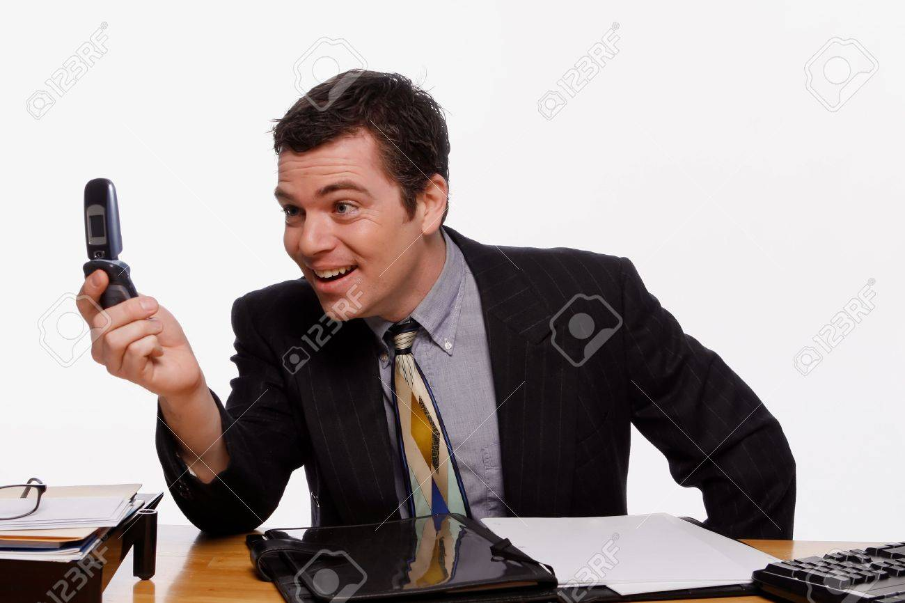 Businessman looking at his cellphone screen with a crooked smile on his face. Isolated against a white background. Stock Photo - 3002684