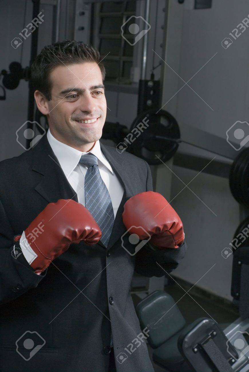 Confident attractive man in a business suit and wearing boxing gloves. Shot is set in a gym and he has a big smile on his face Stock Photo - 3023577