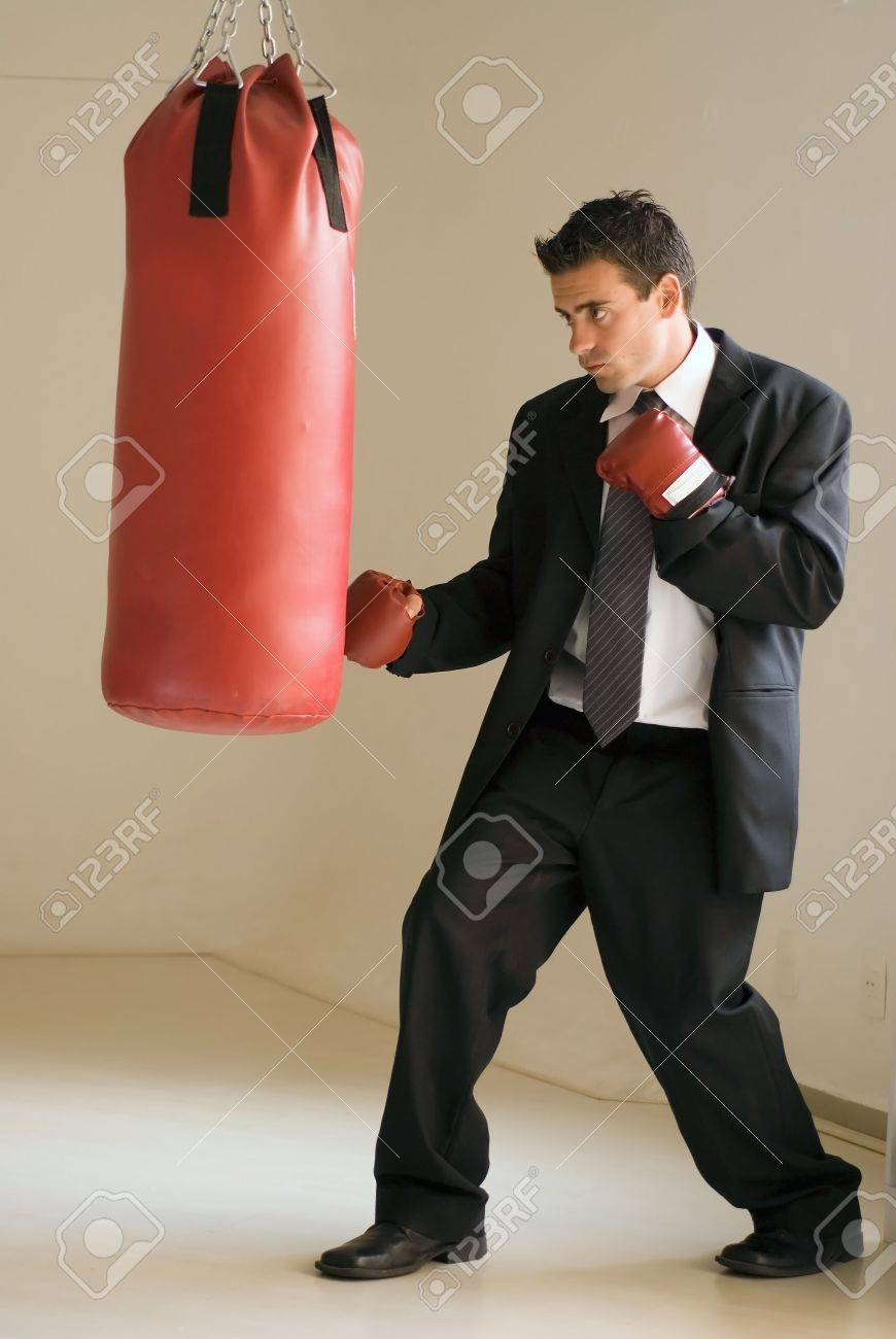 Young Attractive Businessman Throwing A Punch At A Heavy Punching Bag Stock  Photo   3041998