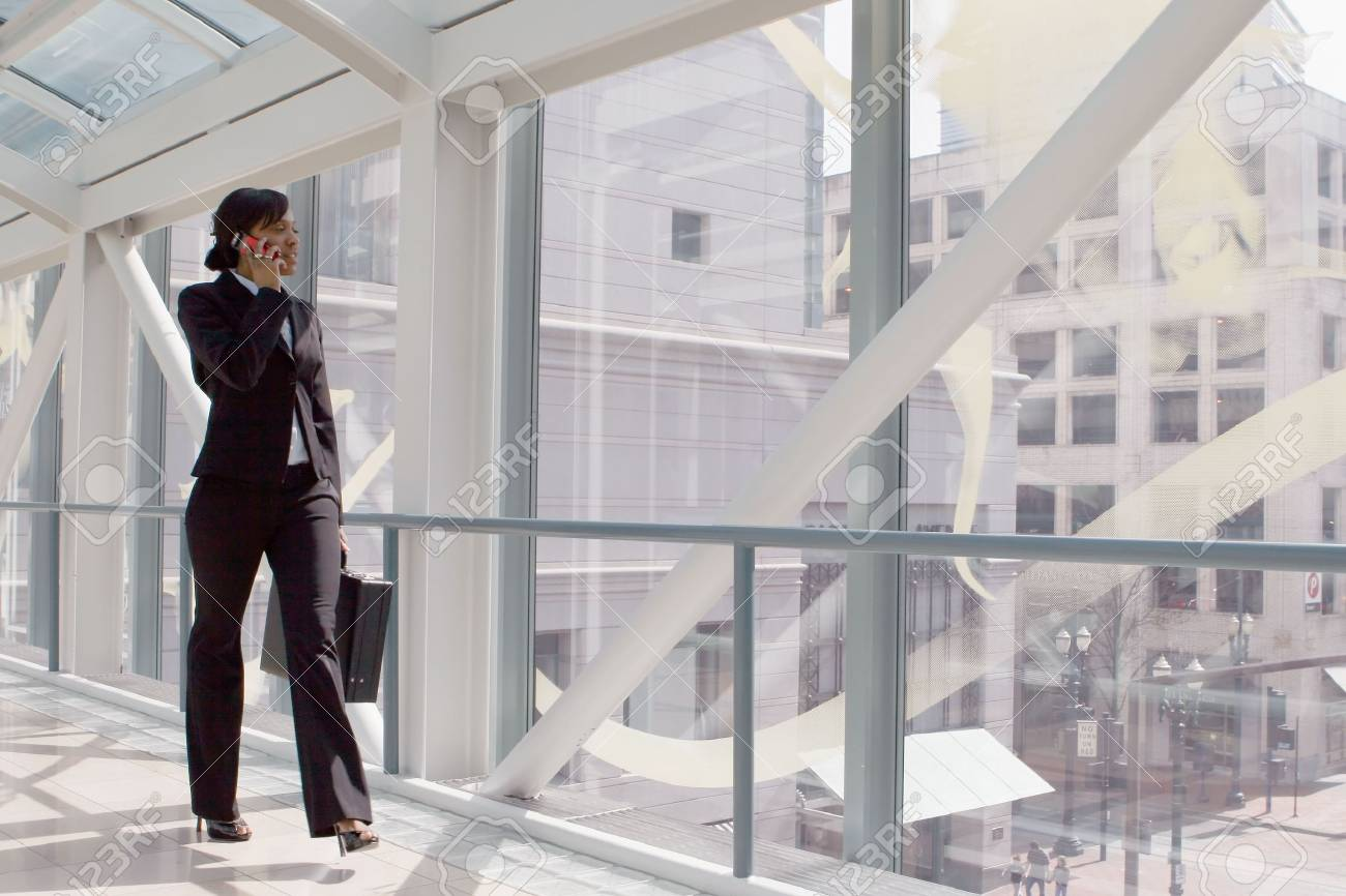 Horizontal shot of a businesswoman, talking on a cellphone, walking through a skybridge Stock Photo - 3116435
