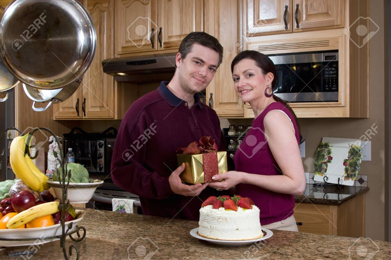 Attractive couple exchanging a gift and sharing a cake in their kitchen. Both are looking at the camera with a neutral expression. Horizontally framed shot. Stock Photo - 3132505
