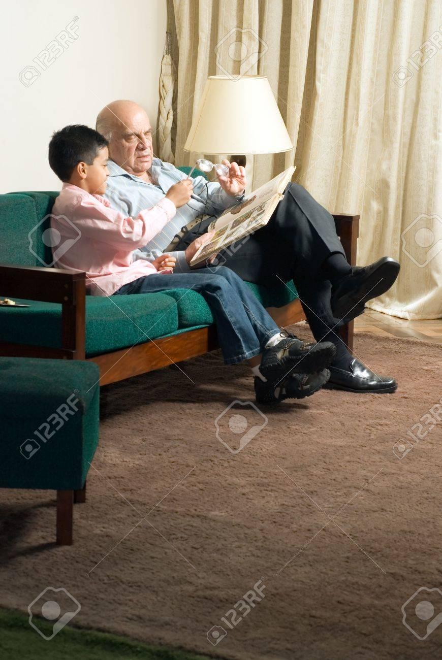 Großvater Und Enkel Sitzen Auf Der Couch Ein Buch Zu Lesen ...