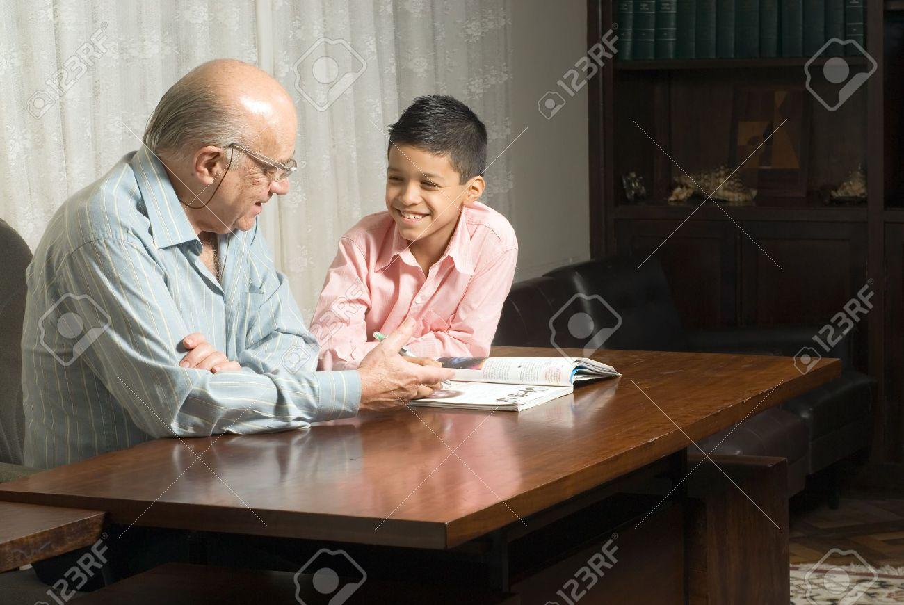 Großvater Und Enkel Sind Am Tisch Ein Buch Zu Lesen. Großvater ...