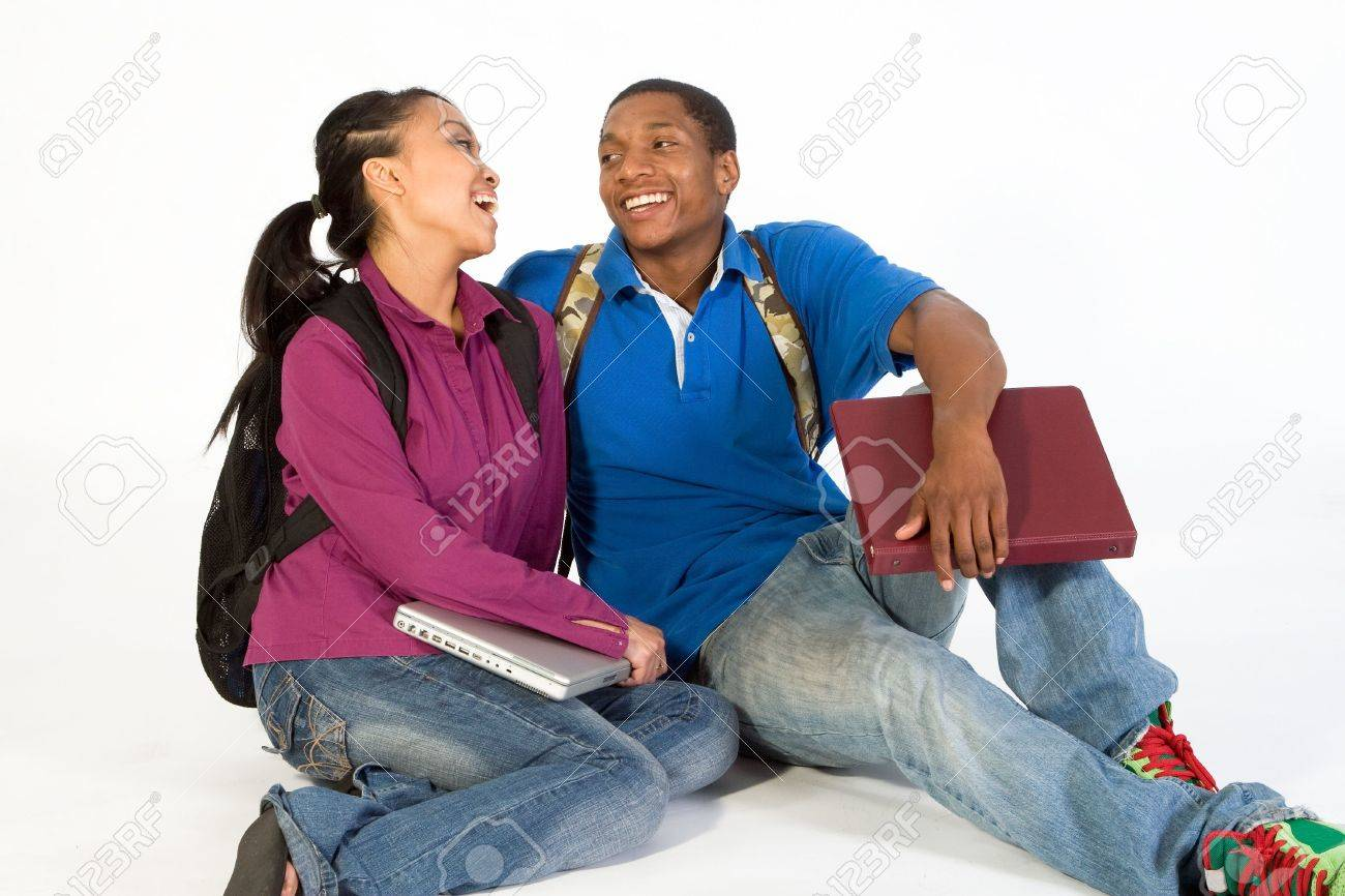 Two Students are sitting on the ground looking at each other. Both wear backpacks and he carries a notebook. Horizontally framed photograph Stock Photo - 3212882