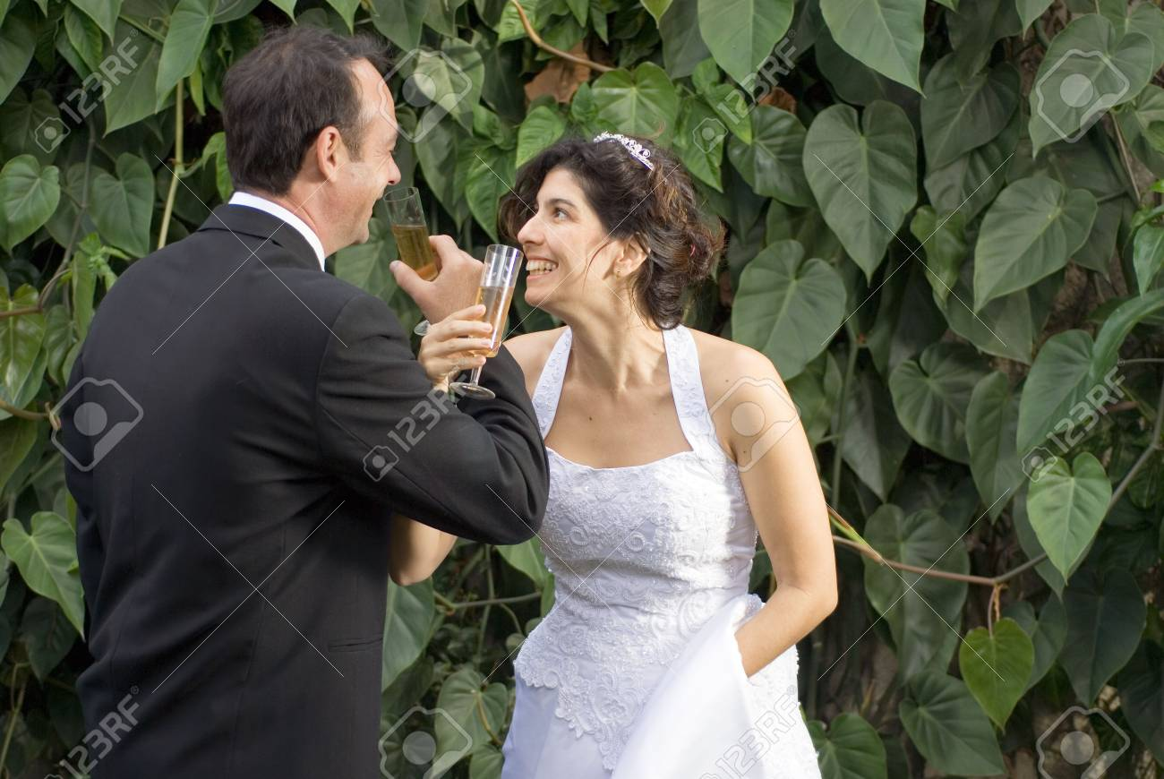 Newly weds drink, while crossing arms, still in their wedding clothes. - horizontally framed - 3263909