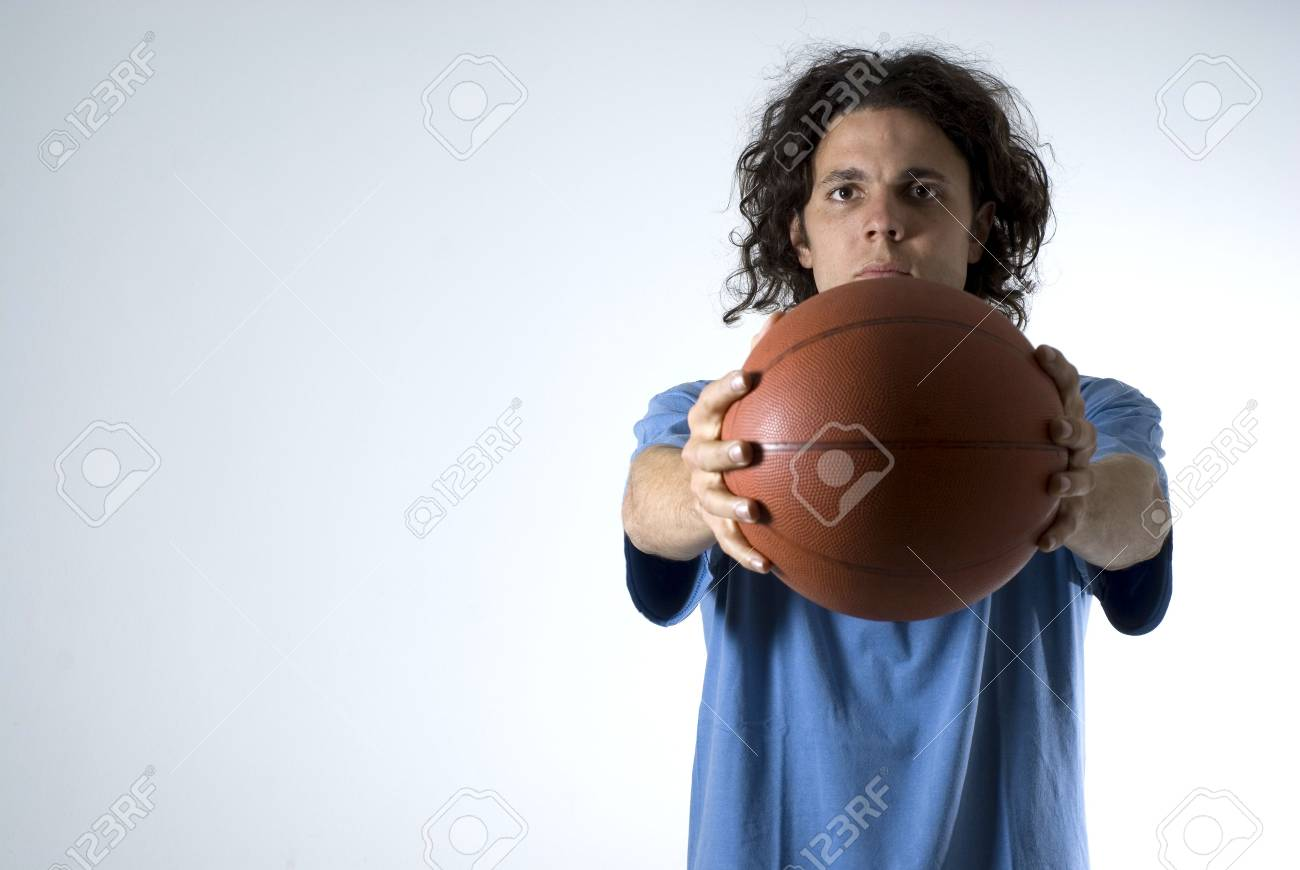 Man holding a basketball out with both hands out in front of him. Horizontally framed photograph. Stock Photo - 3334447
