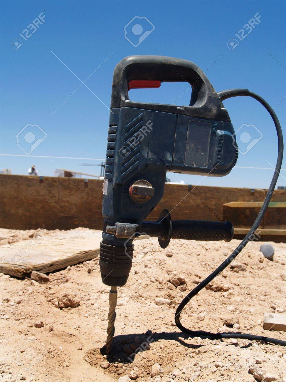 A power drill is sticking upright into the earth.  Vertically framed shot. Stock Photo - 3364689