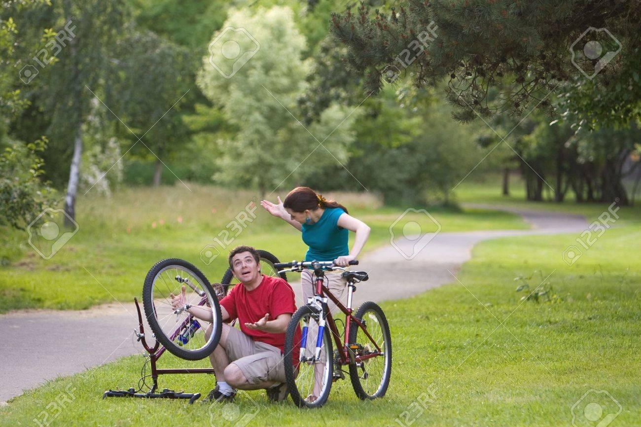 Ein Mann, Sitzen, Versucht Sein Fahrrad Zu Reparieren, Während Es ...