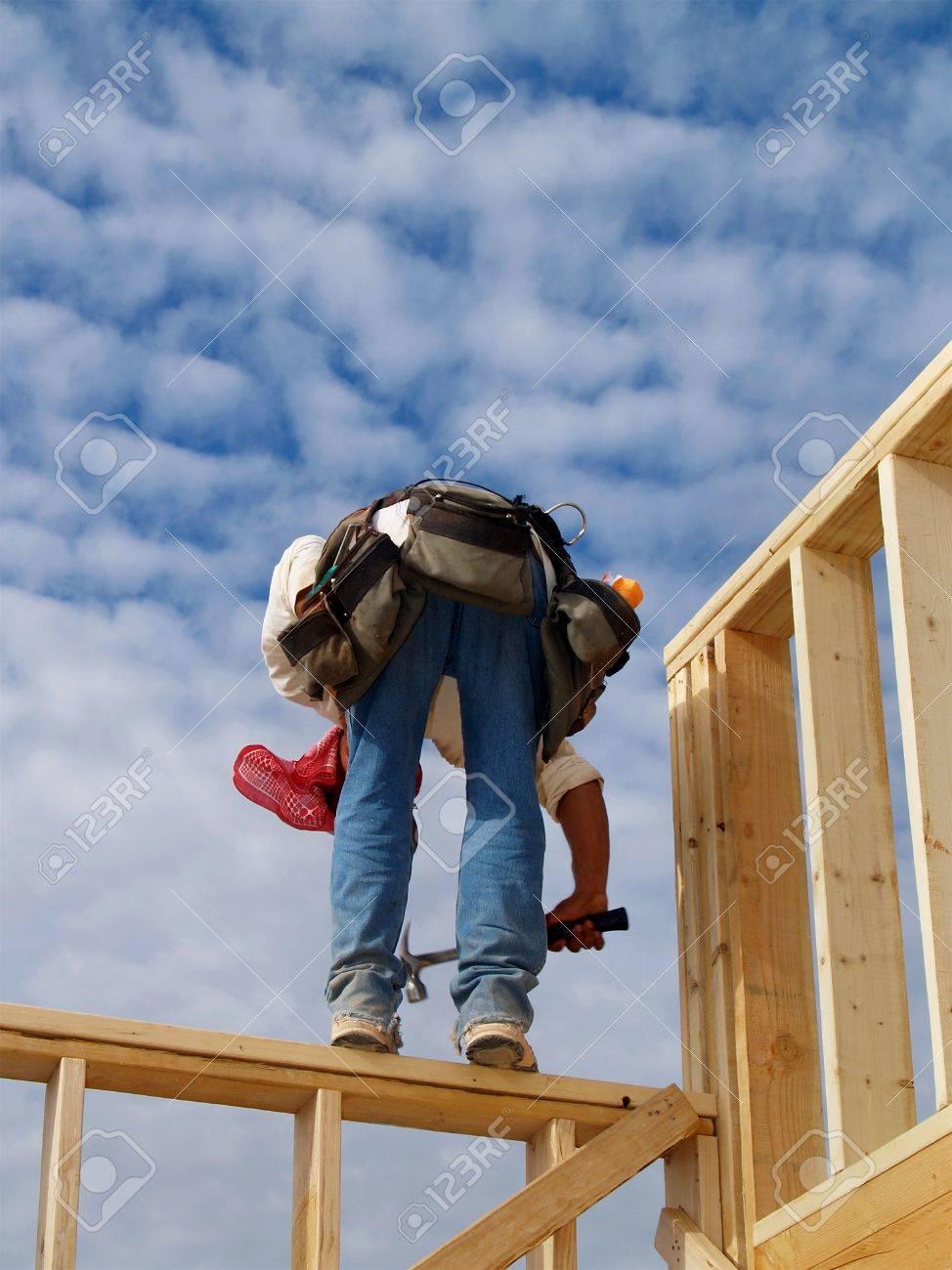Ein Mann Steht An Der Wand Rahmen Eines Hauses. Sein Rücken Ist Vor ...