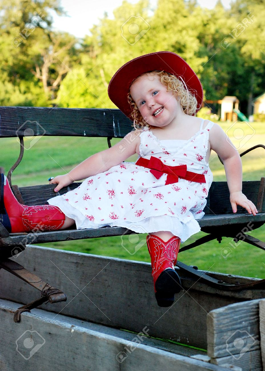 Little Girl Sitting With A White Dress, Red Cowboy Boots And ...