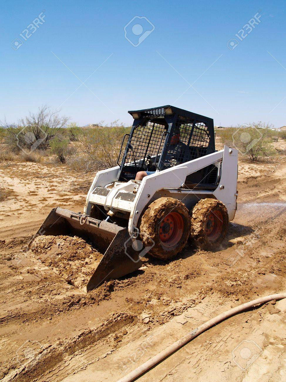 Construction worker driving a skid steer loader at a desert construction site. Vertically framed shot. Stock Photo - 3418500