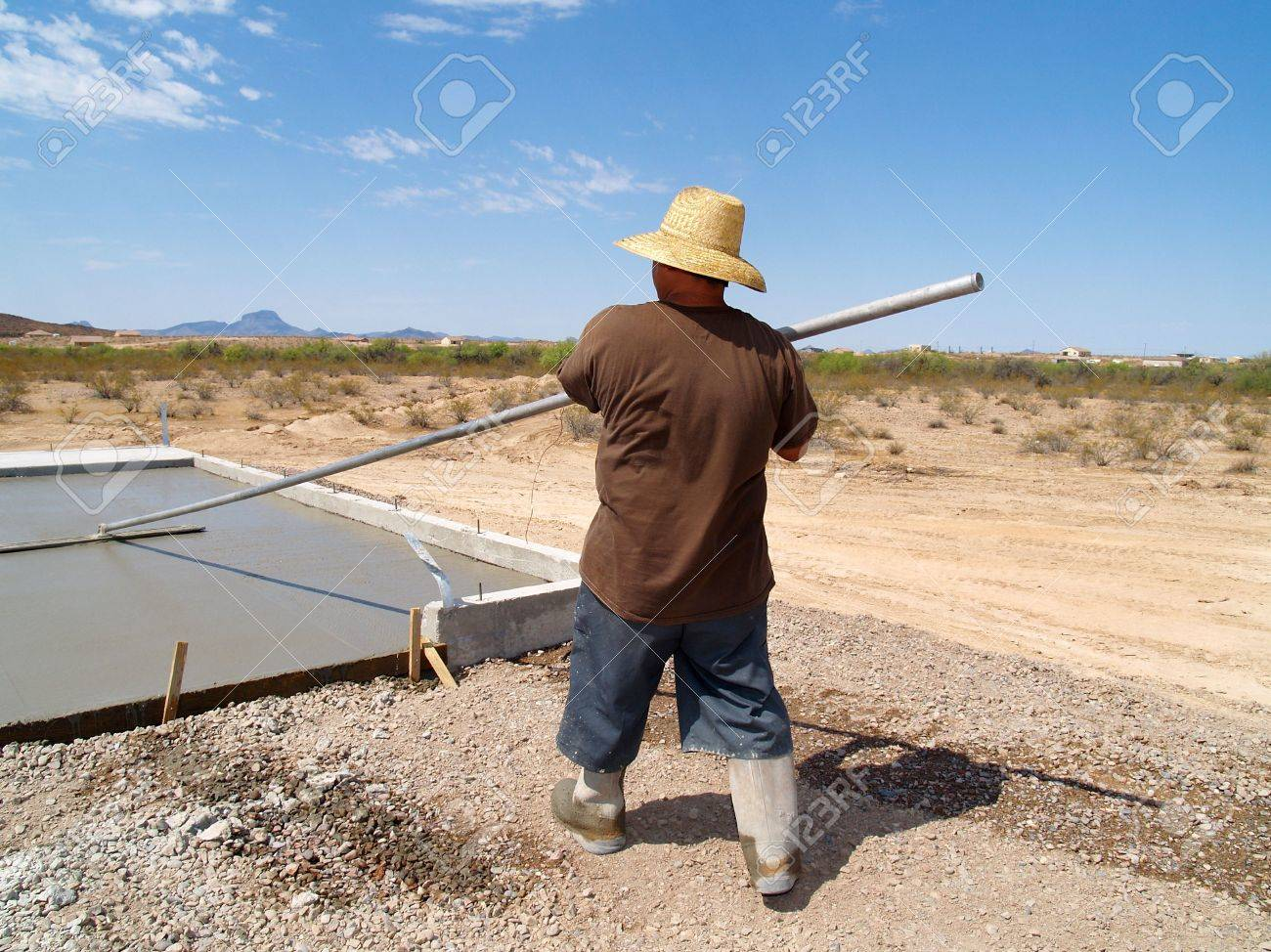 Construction worker smoothing out a freshly poured concrete slab. Shot is set in a desert. Horizontally framed shot. Stock Photo - 3418486