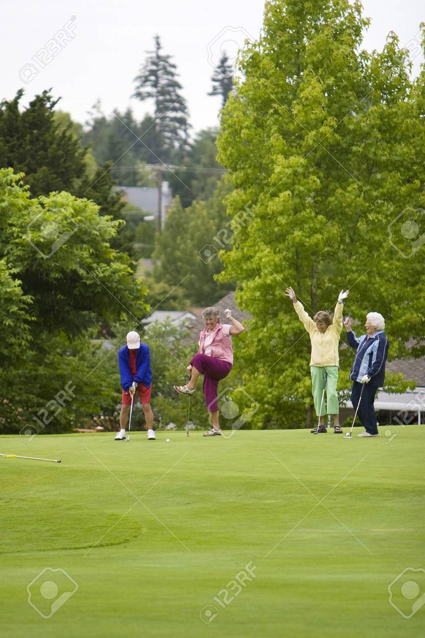 Group of four women celebrating with their arms up while playing golf. Vertically framed photo. - 3526151