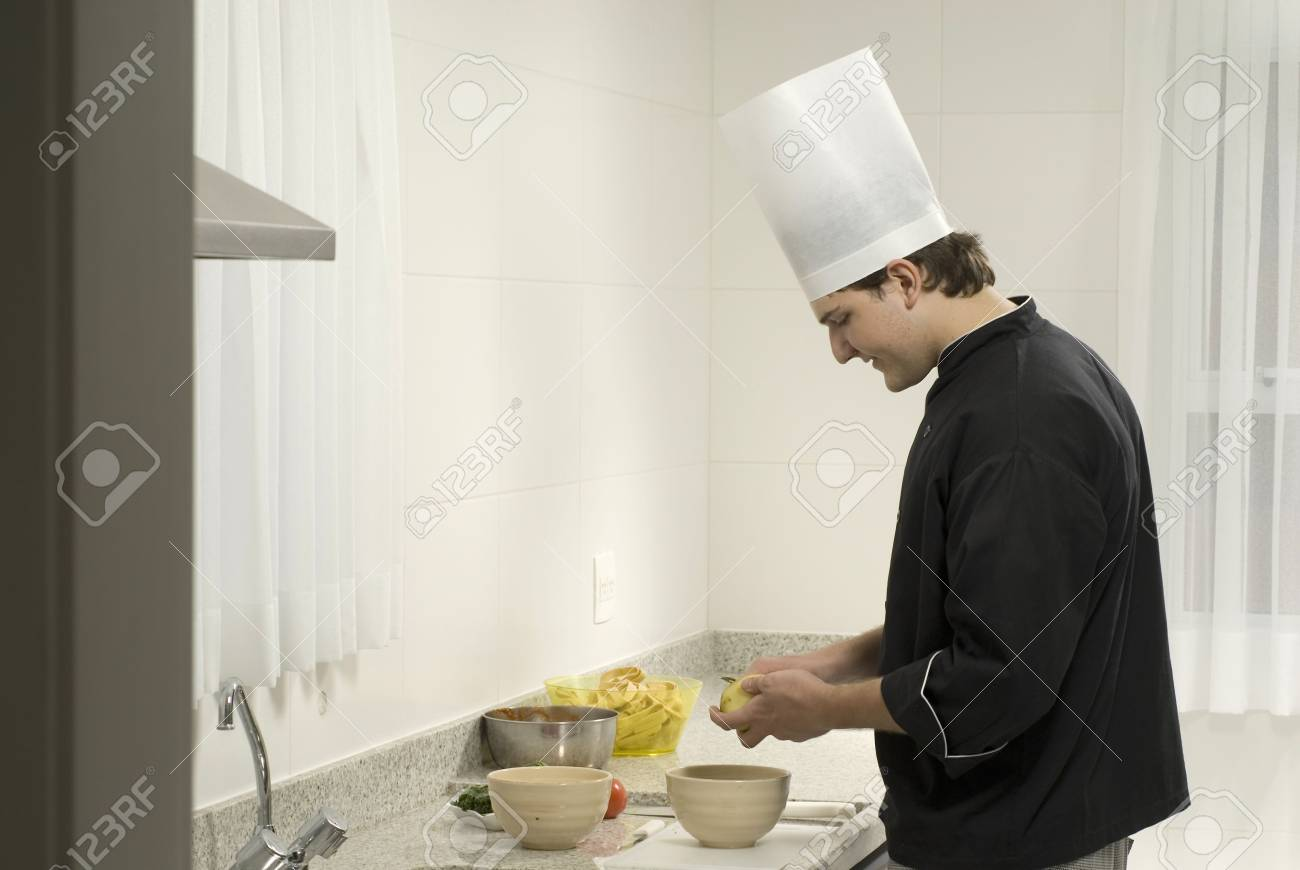 Young, smiling, chef  peeling potatoes into a bowl on a counter next to a bowl and tomatoes. Horizontally framed photo. Stock Photo - 3878246