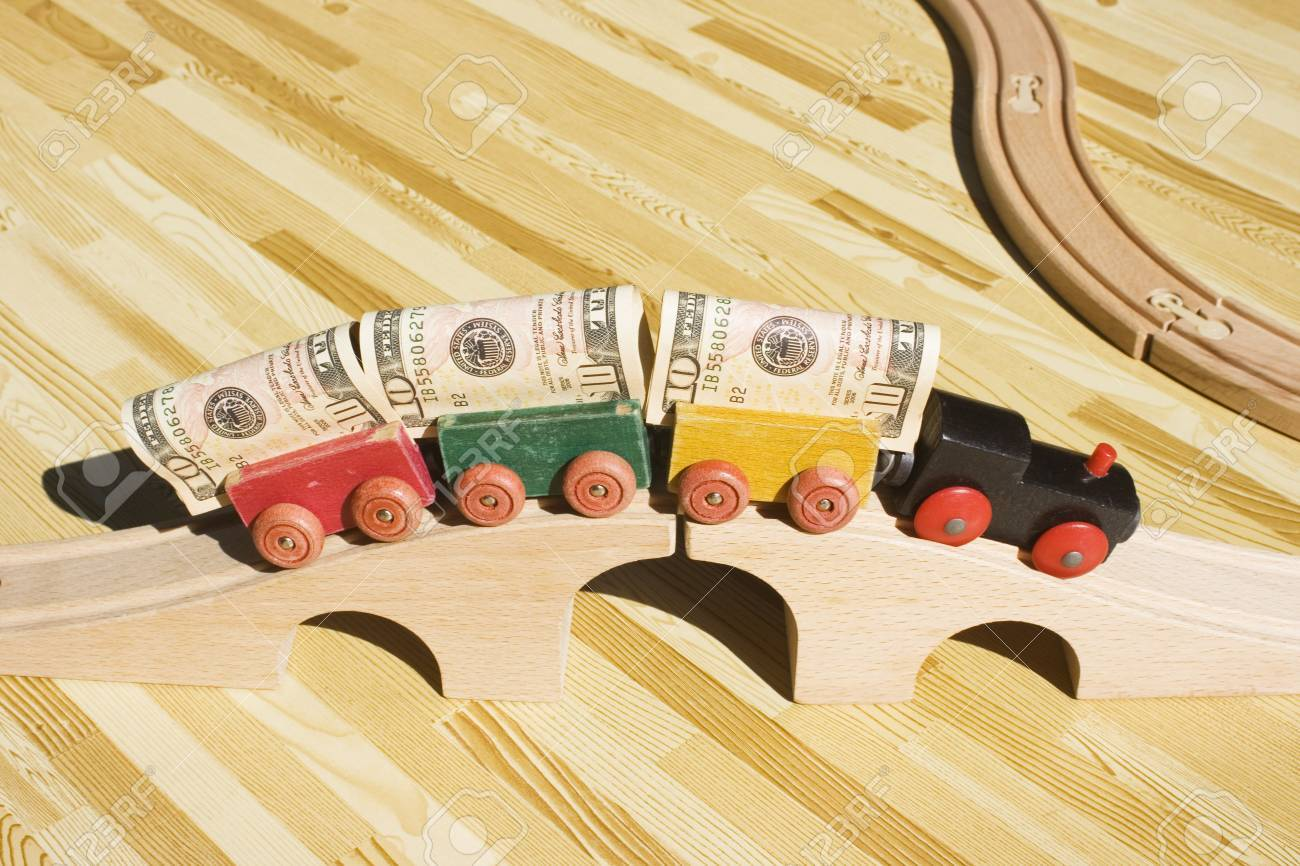 A toy train pulling a cargo of money and going over a bridge.  This picture could be a reference to 'bridging loan','money delivery', gravy train, cargo, freight.  Also, money supply and transfering money. Stock Photo - 4018228