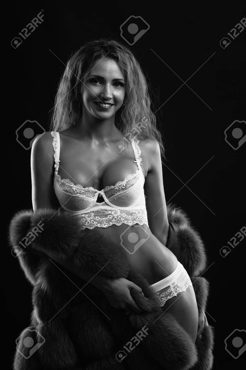 1af012cd6ca Stock Photo - Woman in lingerie posing on a dark background in the studio.  Black and white photo.