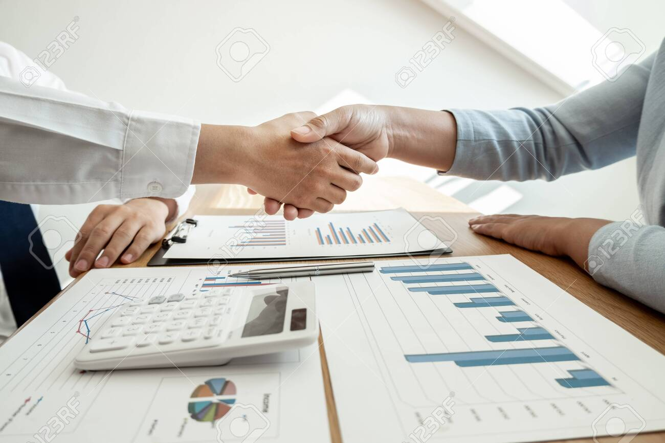 Shaking hand, Two business leader discussing the charts and graphs showing the results, Planning to start new strategy for big success. - 135704485