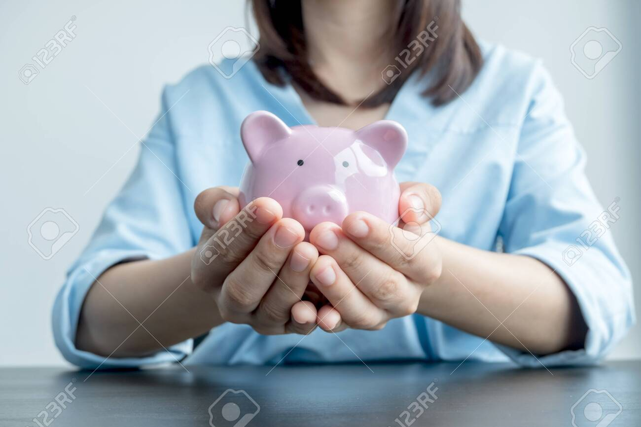 A woman's hand holds a piggy bank for saving into a growing business to succeed and save for retirement. - 153458873