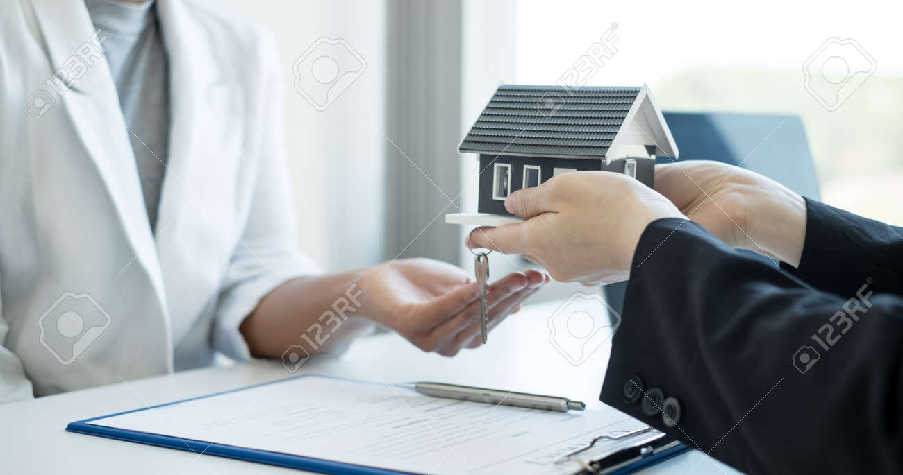 Real estate agent broker hand over the home to the new owner after completing the signing according to agreement renting a house and buy house insurance Home insurance concept. - 166531681