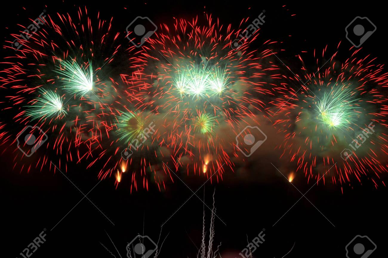 Colorful fireworks that explode and fill the darkness of the night sky with colored light. - 136251090