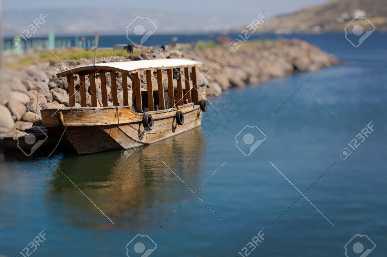 Single ancient boat on the see of galilee with reflection in the water Stock Photo - 13309237