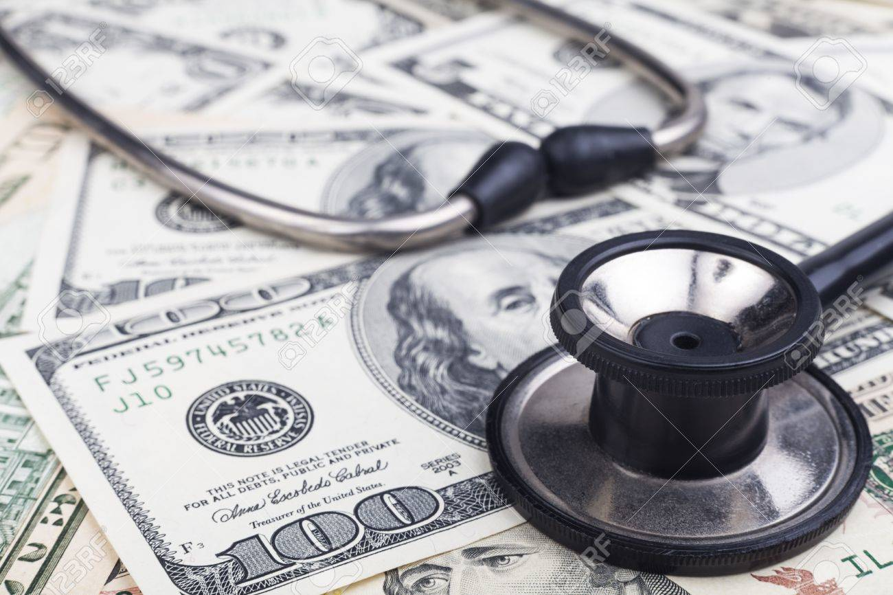 Black stethoscope close-up on top of Dollar banknotes side view - 15540139
