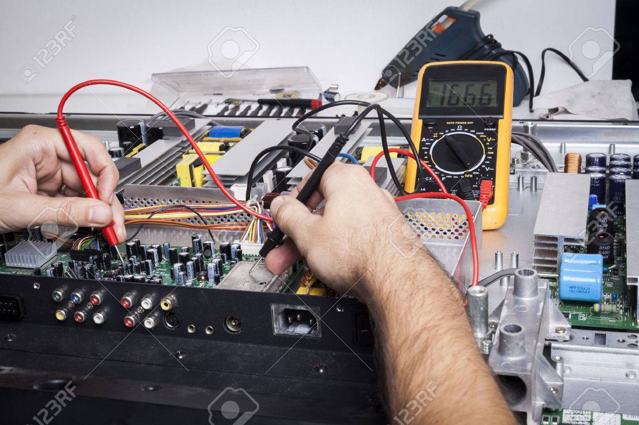 Electronics Repair service with red probe and capacitors on electronic