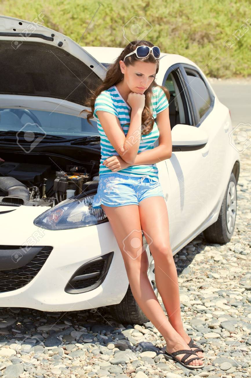 Young brunette woman is standing near broken car - 13917733