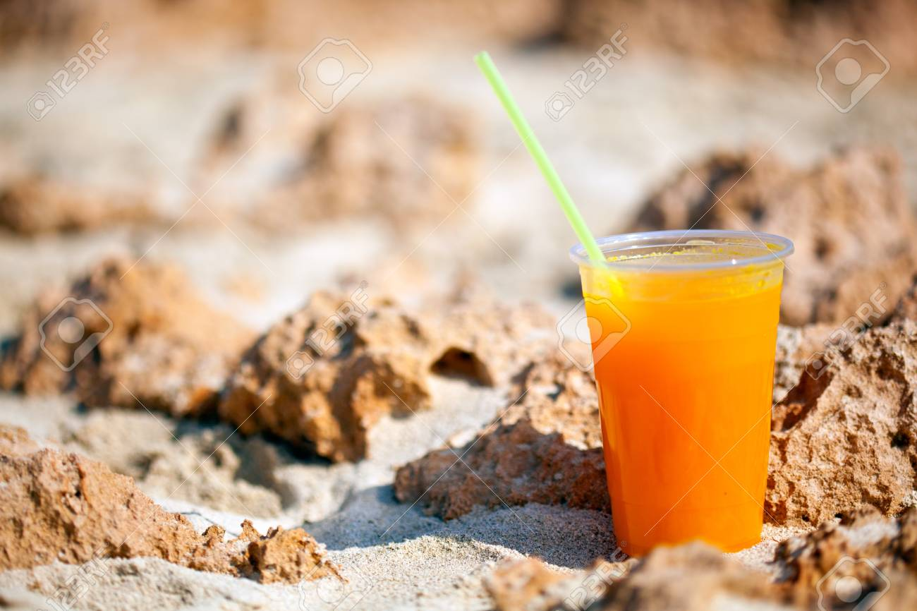 A glass of juice is standing on the beach Stock Photo - 14009606