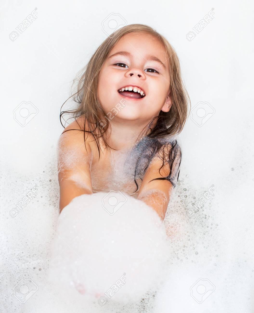 happy little girl is taking a bath with a foam - 87638923