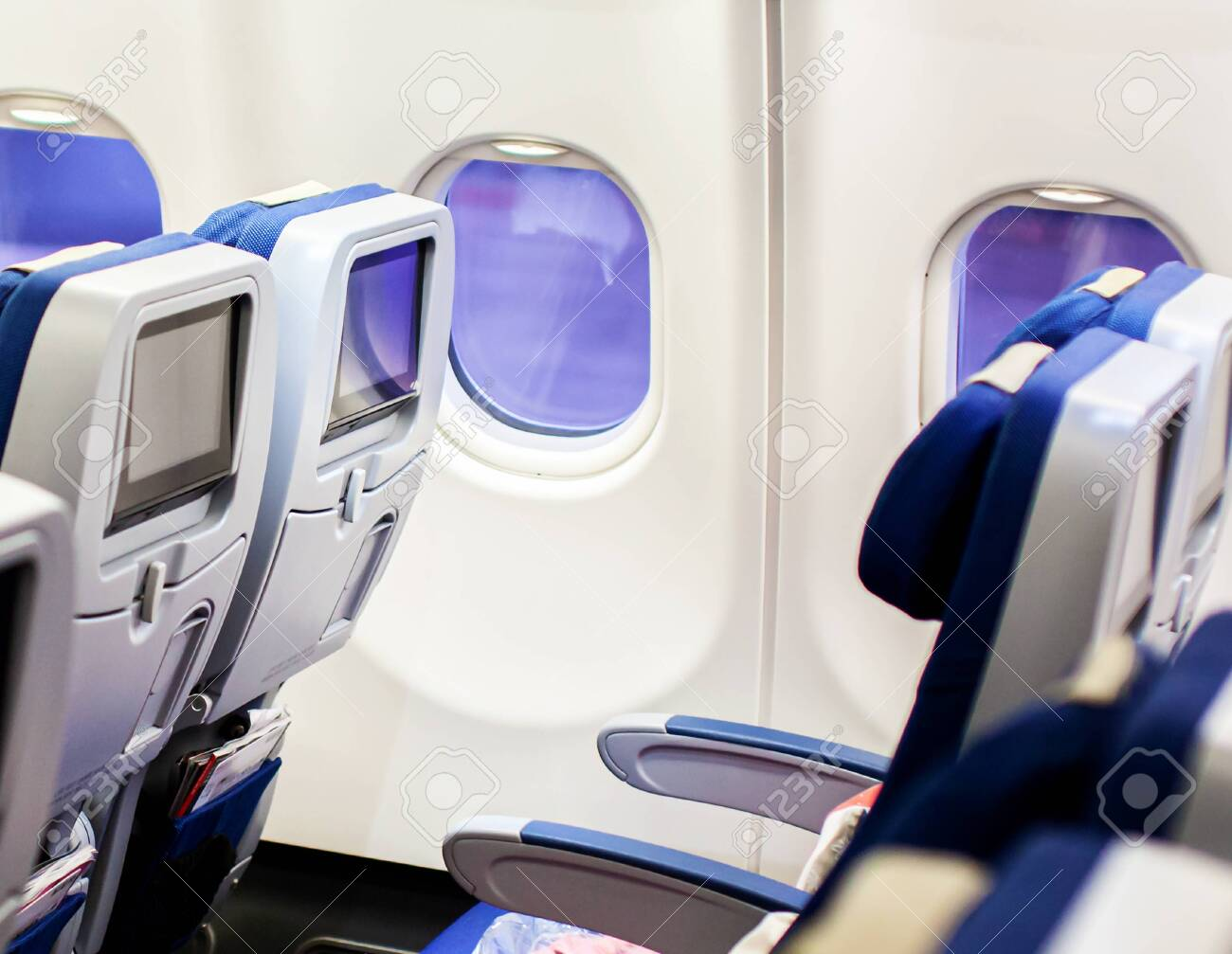 Aircraft interior with seats and blank touch screens displays. - 130370649