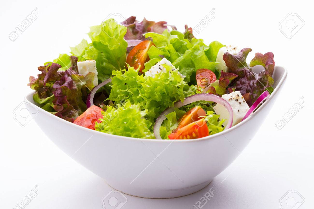 mixed vegetable salad with tomatoes, onions, and feta cheese in a white bowl on white background - 55387759