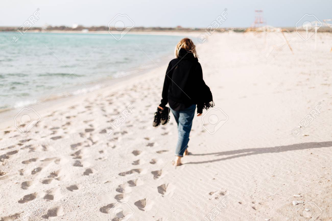 ed9d5c5a8 A Young Girl Walks Along An Empty Beach Alone. Shoes In Hand ...