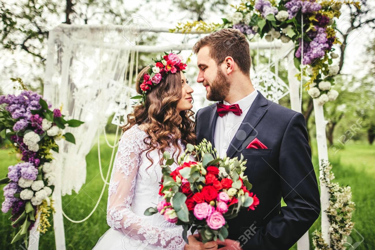 bride and groom outdoors. wedding ceremony. wedding arch. - 64056684