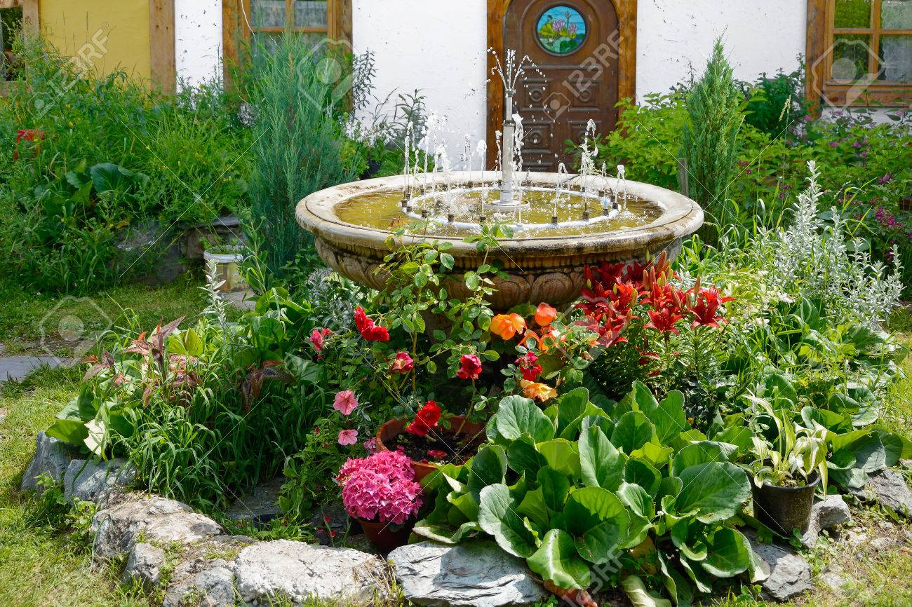 Vase With A Decorative Fountain In The Middle Of A Flower Bed ...