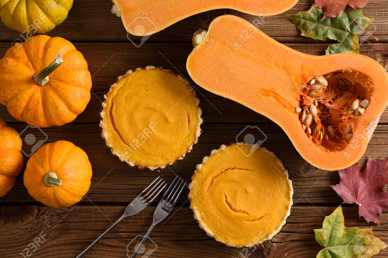Small Simple Pumpkin Pies With Decorative Pumpkins And Butternut Squash On Rustic Wooden