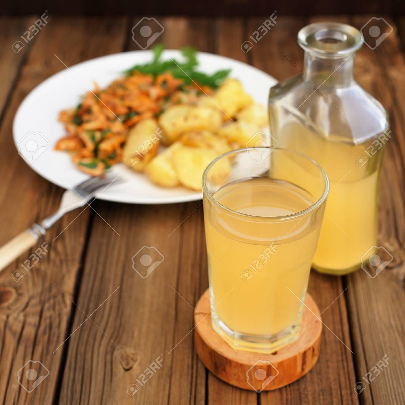 Kvass - cold Russian beverage of rye bread - in glass and bottle with  roasted potatoes