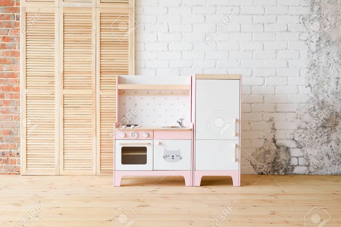 Play kitchen for children. Pink and white wooden toy kitchen..
