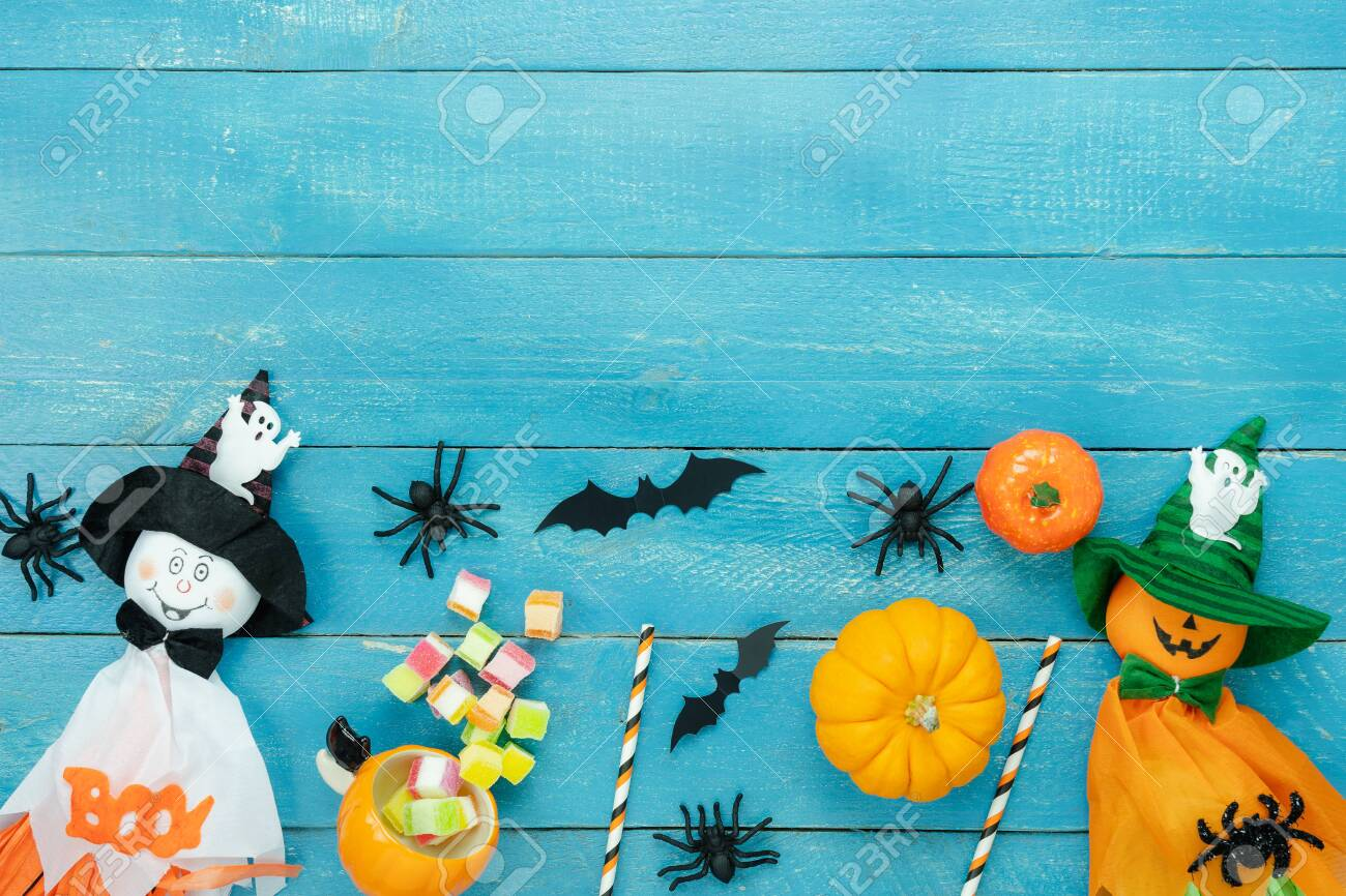Table top view aerial image of decoration Happy Halloween day background concept.Flat lay accessories essential object to party the pumpkin & doll and candy on blue wooden.Space for creative design. - 131764657