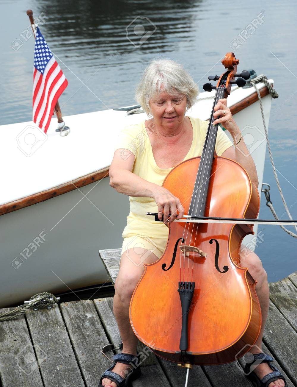 Female cellist performing on the lake. Stock Photo - 11071296