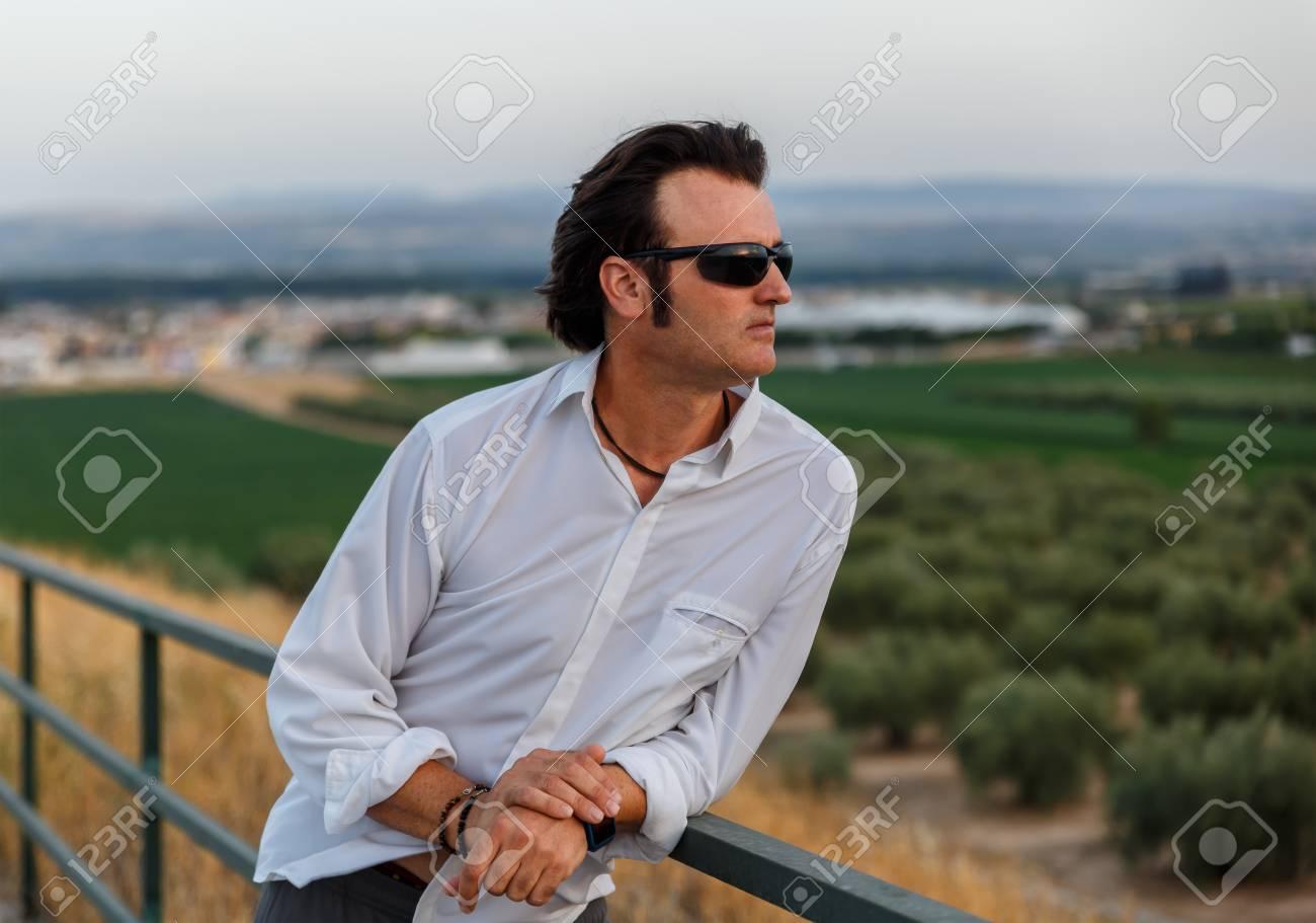 Un homme brun avec des lunettes de soleil appuyé sur une balustrade au milieu de la nature