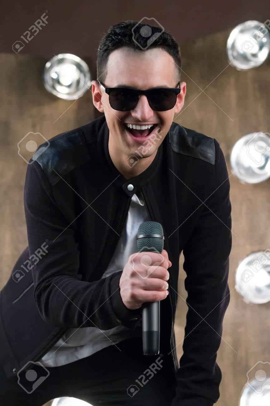 4d7a3536de4e7a Banque d images - Homme chanteur de rock ou de pop vêtu de noir et des  lunettes de soleil avec microphone joue sur scène avec des projecteurs  éclaircissants ...