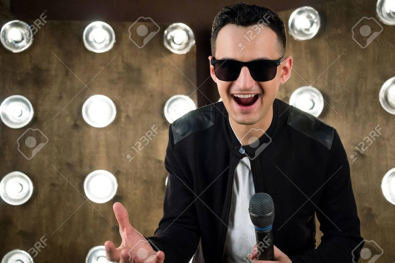prix incroyable haut fonctionnaire moitié prix Homme chanteur de rock ou de pop vêtu de noir et des lunettes de soleil  avec microphone joue sur scène avec des projecteurs éclaircissants sur fond
