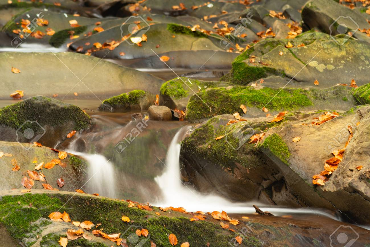 Small mountain waterfall in autumn. A beautiful landscape full of peace. Looking at the mountain stream, you can relax and think. - 111411298