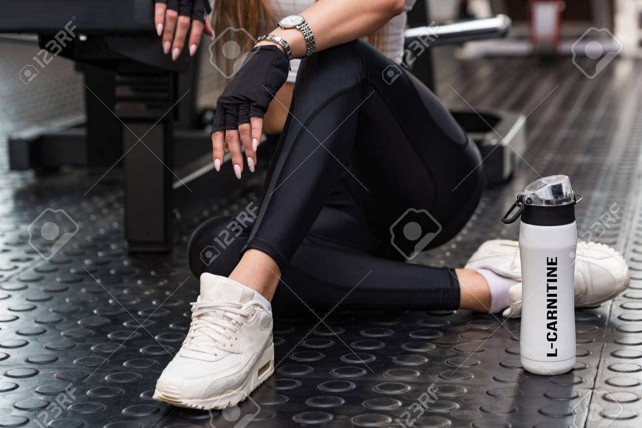 Attractive model sits with L-carnitine drink in modern gym. Lower part view - 120988247